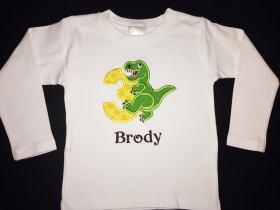 Applique design with Number and dinosaur.  Fabric colors of yellow polka dot and green